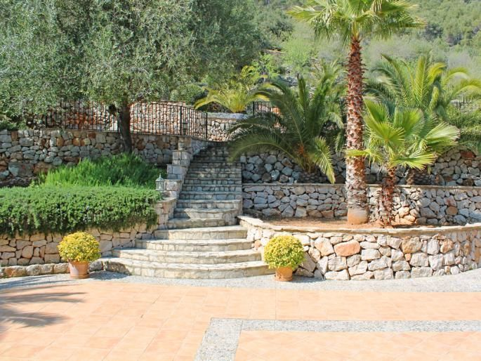 Natural stone walls give this outdoor living area & terrace in