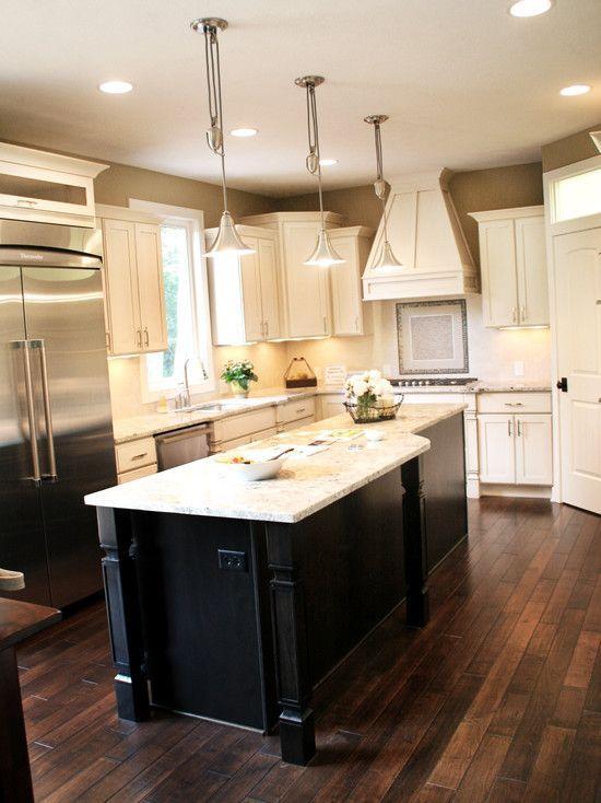 Dark Wood Floors with cream cabinets and dark island   Kitchen