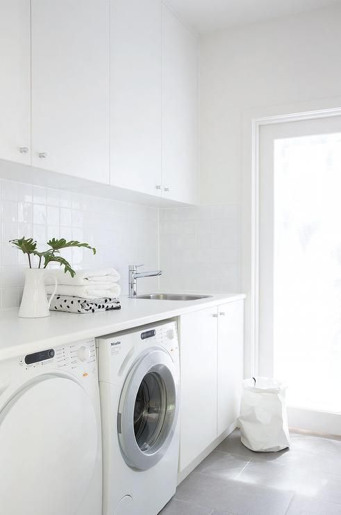 Modern white laundry room features white cabinets paired with white