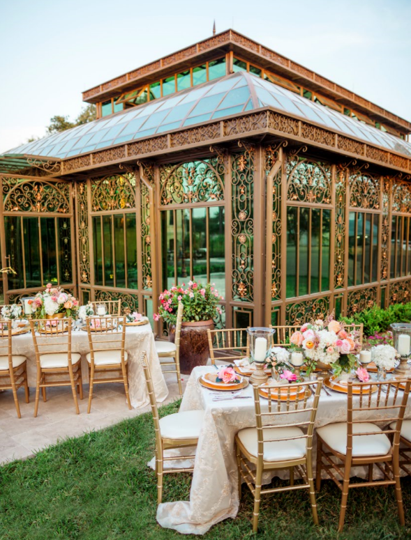 The table decor and golden chairs look perfect with the exterior of