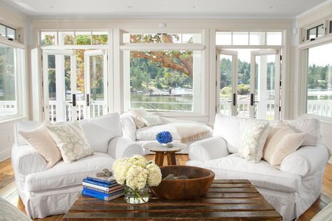 Comfy sunroom white sofa chair. dark wood coffee table and wooden